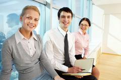 portrait of business partners looking at camera while sitting by the window - stock photo
