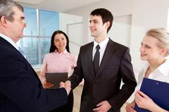 photo of successful business partners handshaking after striking great deal with - stock photo