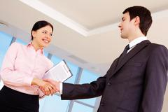 photo of partners handshaking after signing contract - stock photo