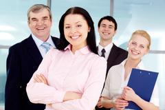 portrait of pretty brunette looking at camera with business team behind - stock photo