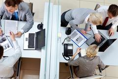 above angle of two business teams working at tables separated by border in offic - stock photo