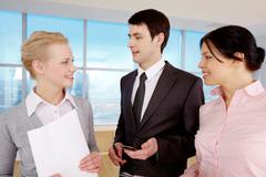 Portrait of businessman explaining work to his colleagues Stock Photos