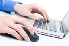 close-up of male hand pressing buttons of computer mouse and keyboard of laptop - stock photo