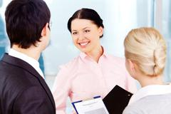 photo of smart women looking at her colleagues with smile during dialogue - stock photo