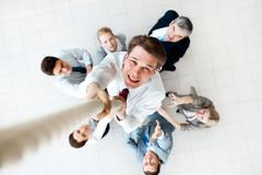 above view of happy employer ascending up the rope with several employees beneat - stock photo
