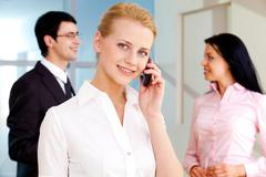image of pretty employee speaking on the phone and looking at camera in working - stock photo