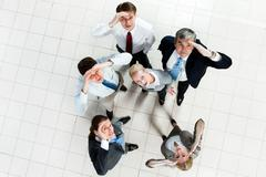 portrait of confused business group standing on the floor and looking at camera - stock photo