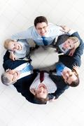 above view of several happy business partners looking at camera while embracing - stock photo