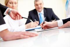 Close-up of business partners hands during planning in working environment Stock Photos