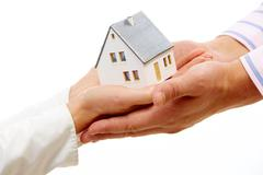 Close-up of female hands passing toy model of house to male Stock Photos