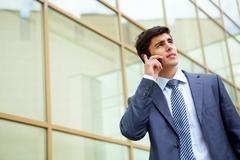 portrait of confident businessman communicating by cellular phone outdoors - stock photo