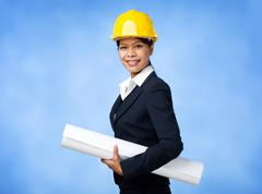 portrait of confident female worker in helmet holding paper - stock photo