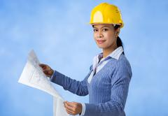 portrait of architect in helmet holding plan of house - stock photo
