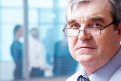 portrait of pensive adult boss wearing glasses looking at camera - stock photo