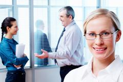 Image of clever woman wearing glasses looking at camera on the background of peo Stock Photos