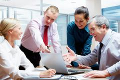 Photo of businessmen showing project at laptop with businesswomen near by Stock Photos