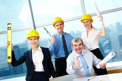 portrait of four happy workers holding papers and rejoicing - stock photo