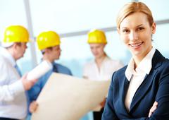 portrait of beautiful architect folding arms on the background of workers - stock photo