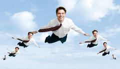 Conceptual image of many businessmen flying in the clouds Stock Photos