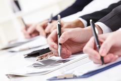 close-up of business person hand working with document - stock photo