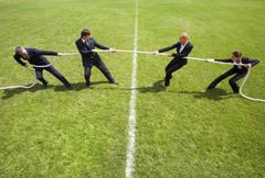 Businessmen and businesswomen playing tug of war Stock Photos