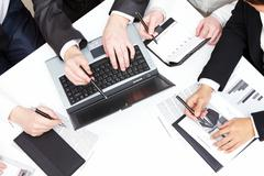 photo of male hand pointing at laptop during group discussion - stock photo