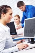 image of secretary typing document on the background of working people - stock photo