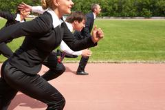 Image of active employees running down sport track Stock Photos