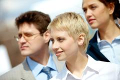 portrait of confident business group looking aside with pretty blonde at foregro - stock photo