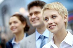 portrait of confident partners looking aside with pretty blonde at foreground - stock photo