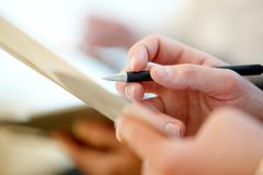 close-up of male hand with pen making notes during conference - stock photo