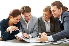 photo of young businessman pointing at document during meeting - stock photo
