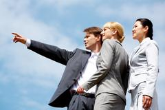 close-up of businessman pointing at something while two elegant ladies looking a - stock photo