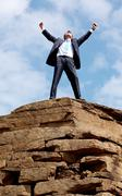 Happy businessman standing on the top of mount with his arms raised to the sky Stock Photos