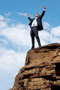 Photo of joyful businessman raising his arms upwards while standing on the rocky Stock Photos