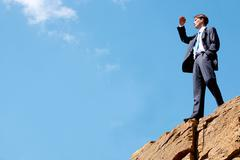 Photo of happy businessman standing on the cliff and looking into the distance o Stock Photos