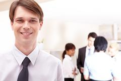 Face of handsome businessman on the background of interacting coleagues Stock Photos