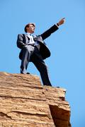photo of serious businessman standing on the cliff and pointing into the distanc - stock photo