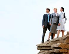 photo of three business partners standing on the mountain top with cloudy sky ab - stock photo