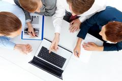 photo of colleagues looking at laptop and discussing new project - stock photo