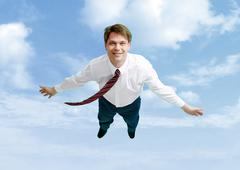 conceptual image of happy businessman flying in the clouds - stock photo