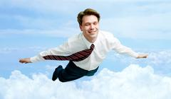 conceptual image of smiling businessman enjoying flying in the clouds - stock photo