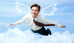 Conceptual image of contented businessman with wings flying in the clouds Stock Photos