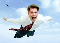 conceptual image of young businessman shouting while flying in the clouds - stock photo