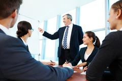 Smart and confident boss pointing at whiteboard while group of employees listeni Stock Photos