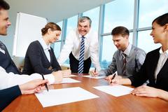 Smart and confident boss looking at managers writing on papers at meeting Stock Photos