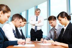 confident boss looking at managers while they writing on papers at seminar - stock photo