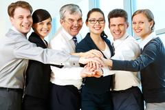 Row of smiling co-workers making pile of hands and looking at camera Stock Photos