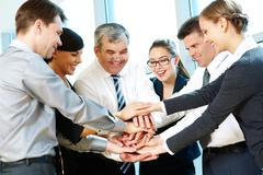 Photo of smiling co-workers making pile of hands and looking at camera Stock Photos
