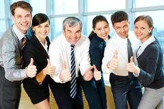 Portrait of happy co-workers looking at camera with smiles and showing sign of o Stock Photos